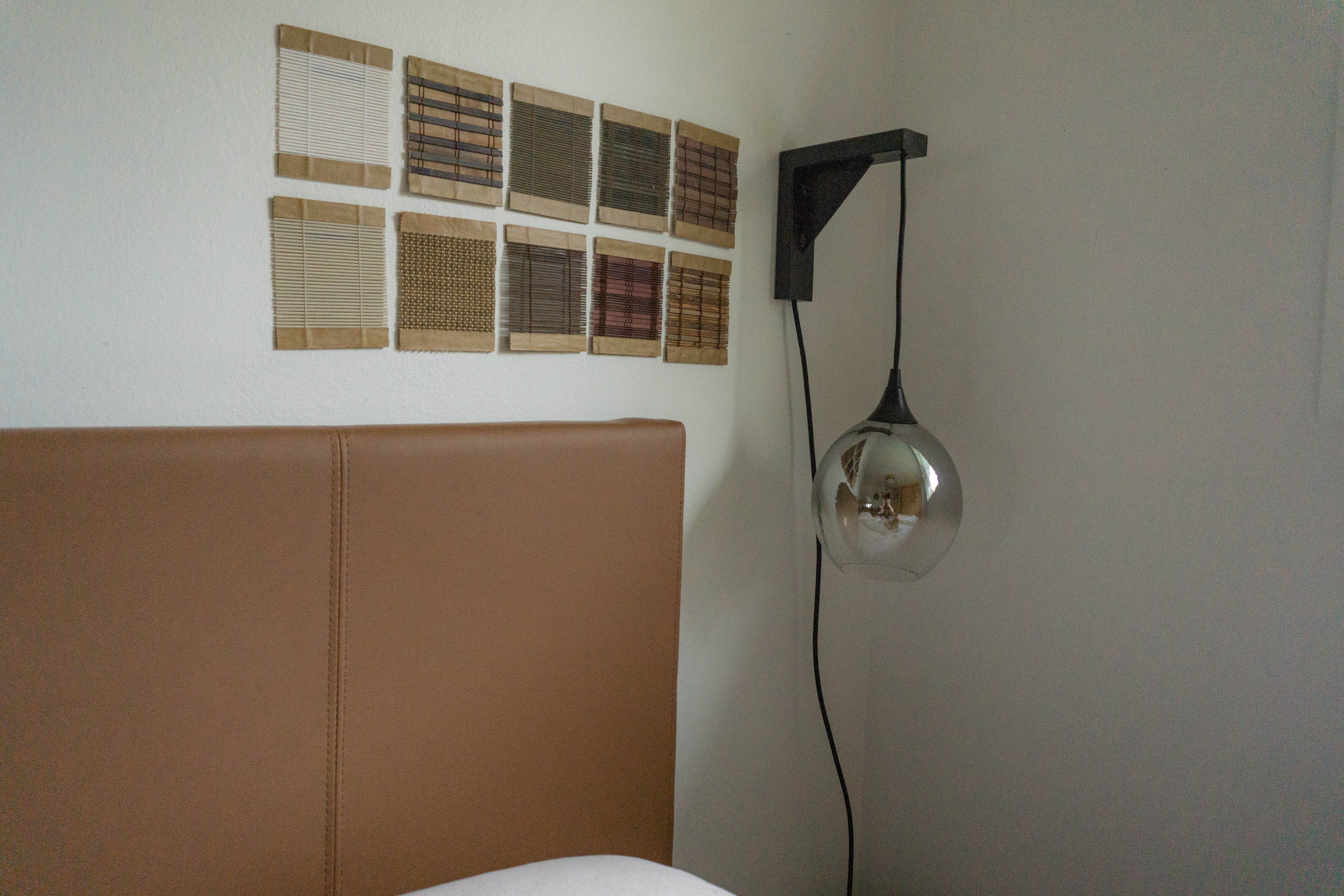Woven Wood Shade Samples on Wall next to Headboard and Sconce