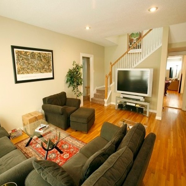 Indoor photo of living room in sober living home with staircase, hardwood floors, flat panel television and nice furniture