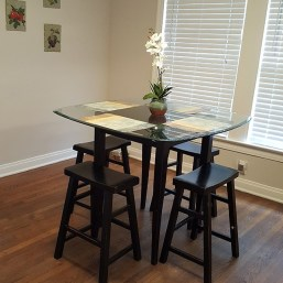 Picture of breakfast room with table and chairs, flowers and windows