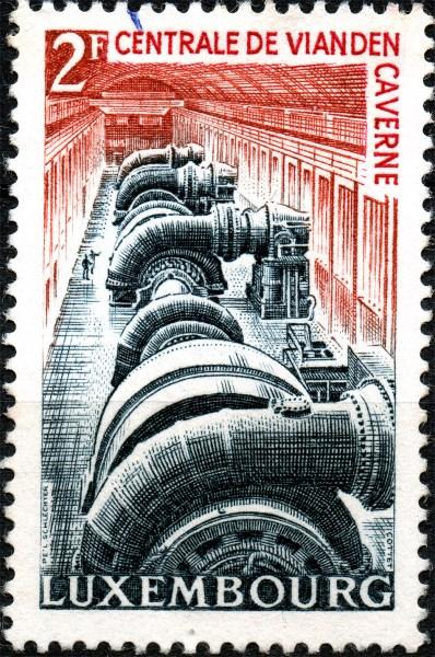 Briefmarke aus Luxemburg. Aus dem Jahr 1964. In Rot und dunkelgrau gehalten. Schöne Gravur die die Turbinen des Turbinenhalle des Pumpspeicherwerk Vianden zeigt. Aufschrift: LUXEMBOURG - CENTRALE DE VIANDEN CAVERNE - 2F.