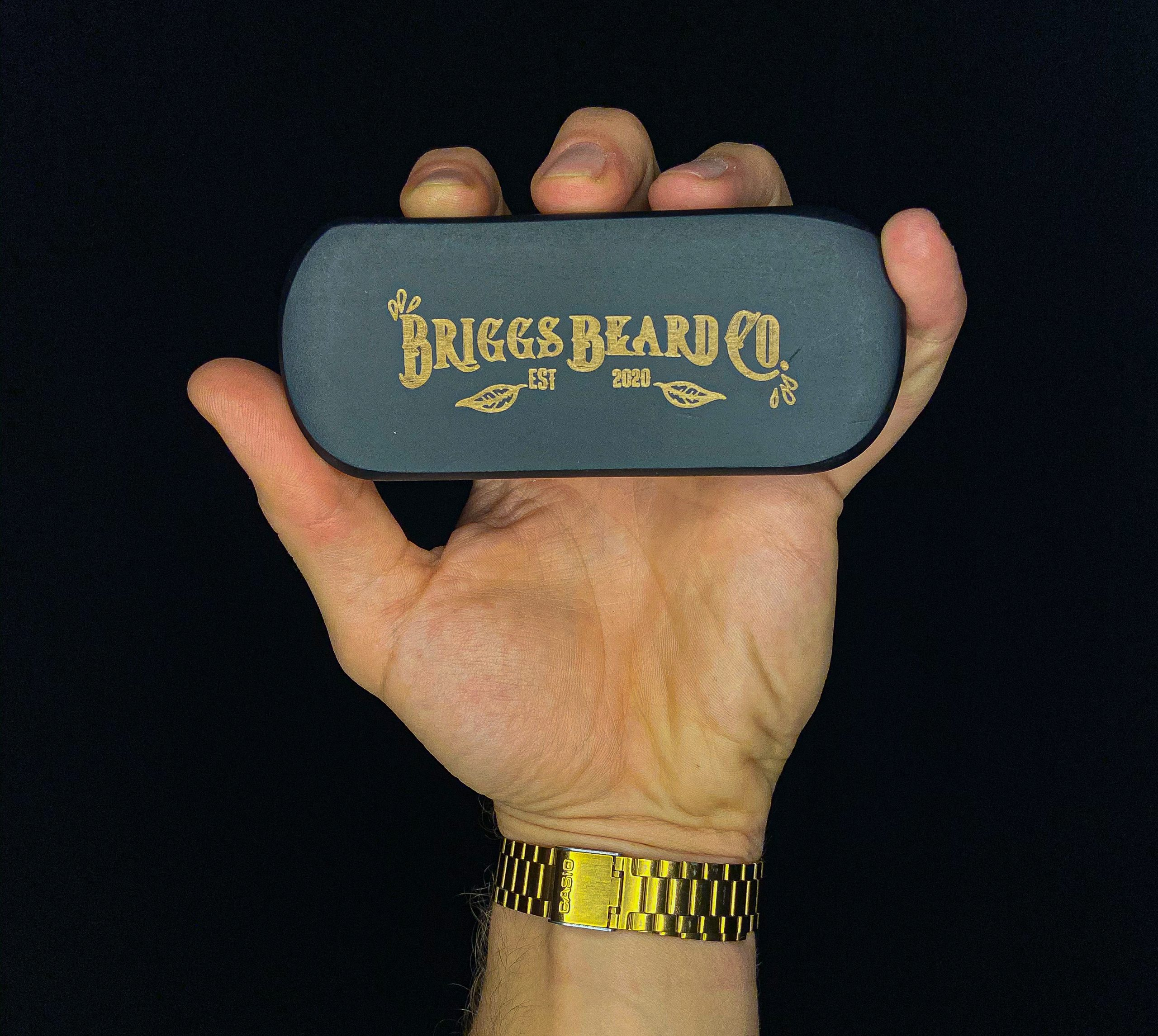 A hand holding the Briggs Beard Co beard brush