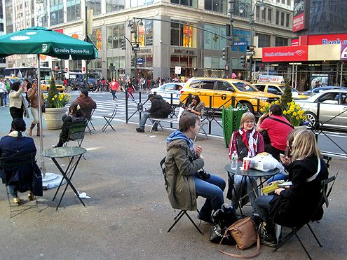 Tables and chairs are placed in the pedestrian plaza allow people to sit and relax