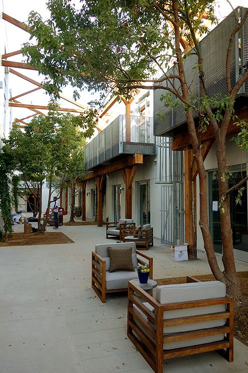 The outdoor furnished courtyard with original historic exposed wooden trusses