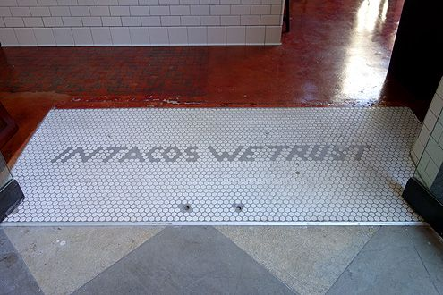In Tacos We Trust greets Guisados customers at the front entrance