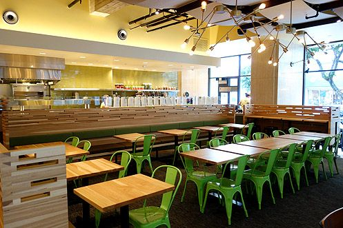 The dining area inside Tender Greens is bright, modern, and comfortable