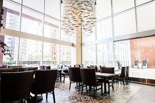 A beautiful chandelier composed of white fishes hangs over the dining area adjacent to the office lobby (Photo: Wonho Frank Lee | Eater LA)