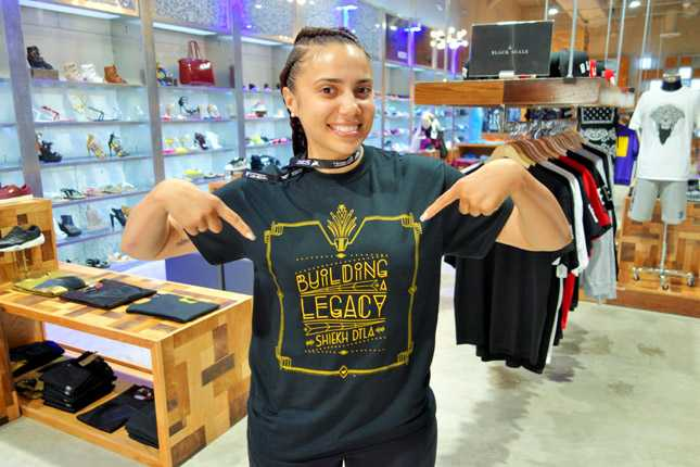 "Store associate Brandi shows off her new DTLA Shiekh flagship store shirt titled ""Building Legacy"""
