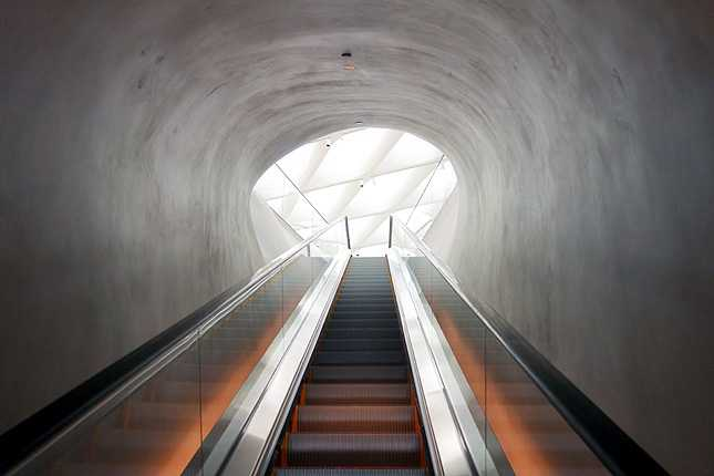 Take the 105-foot escalator up to the main top floor gallery level to begin your museum visit