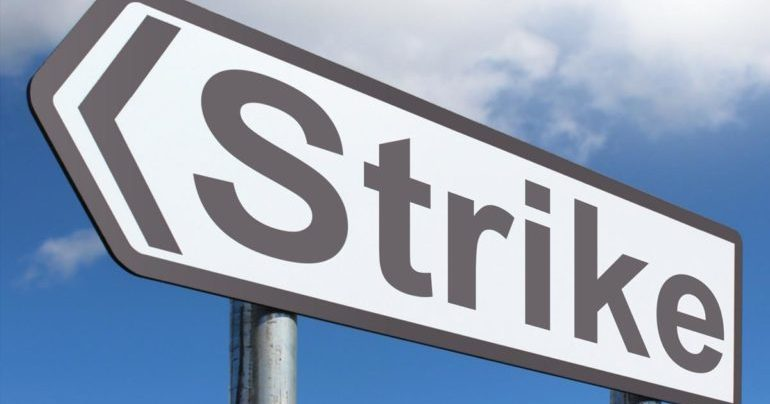A roadsign pointing left with the words strike on it.