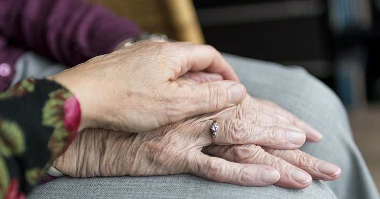 One person's hand comforting another in a care home