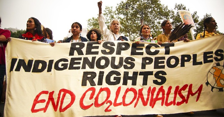 "A protest with a banner reading ""Respect indigenous peoples rights: End co2lonialism."