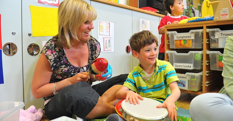 A staff member in children's services playing music with a child