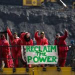 Reclaim the Power activists stood on mining equipment at an open cast coal mine, their banner reads Leeds Reclaim the Power.