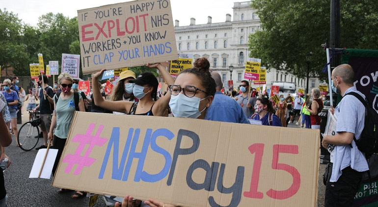 "A photo of protesters with placards reading #NHSPay15 and ""if youre happy to exploit NHS workers and you know it clap your hands"""