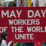 A banner for may day, reads workers of the world unite