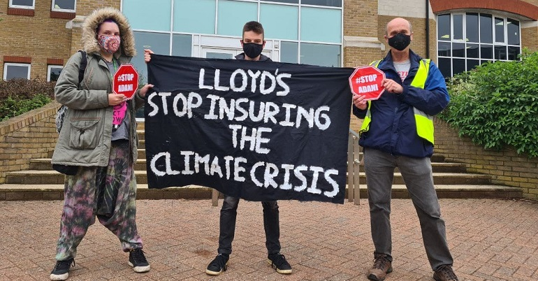 """Climate protesters holding a banner reading """"Lloyds stop insuring the climate crisis"""""""