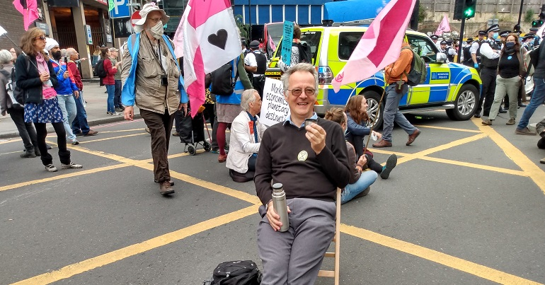 Steve Melia sitting in a blocked road at an Extinction Rebellion protest