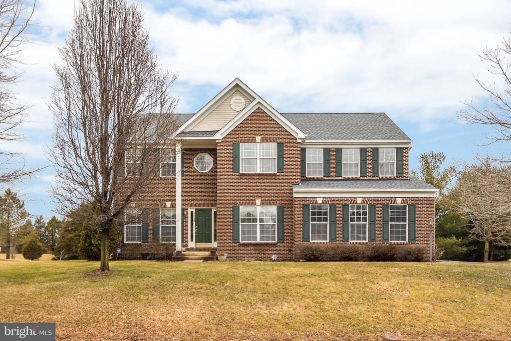 """$10K PRICE REDUCTION!  Beautiful well-maintained brick-front home in quiet golf course community, Bristow Manor Estates. This home is move in ready with high ceilings, tons of natural light, open floorplan and many recent updates. In 2017, Bamboo flooring was installed on the main level, stairs and upstairs hallway, as well as new carpet in the upstairs bedrooms. In addition, a new water filtration system, central vacuum, and new roof were installed. In 2019, carpet in the basement, slate floor in main level powder room, sump pump with back up and fresh neutral paint throughout the home completed the transformation. The kitchen is huge, with granite countertops and loads of cabinet space.  A cook~s dream with double ovens, tons of prep space and a gas cooktop, family meals and entertaining will be a joy.  The first floor study is great for home based businesses and work from home days.  Inspiring views will keep you motivated!  The family room is breathtaking with a two-story stone fireplace, flanked by windows as the centerpiece.  The master bedroom is a spacious relaxing retreat with vaulted ceilings, walk-in closet, and en-suite bathroom with soaking tub. And, the laundry room is on the upper level so more lugging clothes up and down the stairs!  With brand-new carpet and paint, the basement is a clean slate for your imagination.  With a mudroom/gym, full bath, and gorgeous theater room, the possibilities are endless!  A wonderful commuter location, Bristow Manor Estates is mere minutes to retail, restaurants, recreation, entertainment and major commuter routes, yet the """"off the beaten path"""" location has a private, rural, small community feel. Valley View Park and Bristoe Station Battlefield Park, both located within a 2 mile radius, offer sports fields, playgrounds, and walking trails. This home backs to Bristow Manor Golf Course, so you'll enjoy bucolic views from the privacy of your own backyard!  9.25 acre easement to Golf Course.  Owner only maintains and pa"""