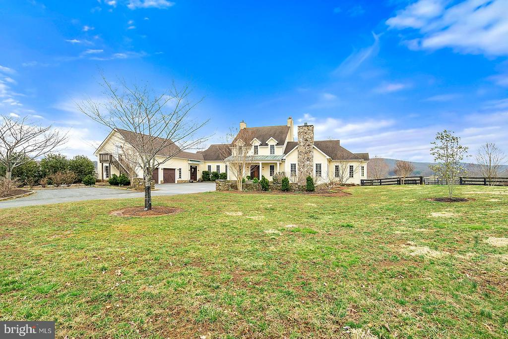 Elegant Country Estate on 102.46  private acres. 2 tax tracts, the house and 44.96 acres and 57.5 acres that has 2 approved drain field sites. The modern farmhouse is designed to take full advantage of the fabulous views of the Bull Run Mountains.  Open floor plan is perfect for entertaining. Luxury master suite with fireplace is on the main level.  Upstairs is the guest suite with full bath, 2 bedrooms that share the balcony and the hall bath.  Lovely playroom at the end of the hall with built-in day bed and shelves, plus a secret stairway to the downstairs den.  The cozy den with vaulted ceiling and exposed beams has a stone fireplace.  The dining room has a wall of windows and stone fire place.  The kitchen and keeping room blend together to make a great spot to gather with a stone fireplace, table space, and seating area.  Butlers pantry with extra dishwasher, wet bar, ice maker and drawer refrigerators.  Kitchen with island has a gas range and oven, plus a wall oven.