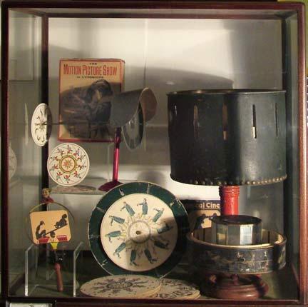 Above is a case containing a selection of our persistence of vision toys. In left of the front row is a Mechanical Cinema toy that spins to show movement by combining the images on two sides of the card. Next is a 19th century Phenakistoscope with a selection of reels. On the right in that row is a Praxinoscope, a drum with a center of mirror facets. Back left is an early 20th century variation of the Phenakistoscope, the Motion Picture Show or Ludoscope. Back right is a large Zoetrope (wheel of life) on a base.  (from website http://brightbytes.com/collection/per_vis.html)