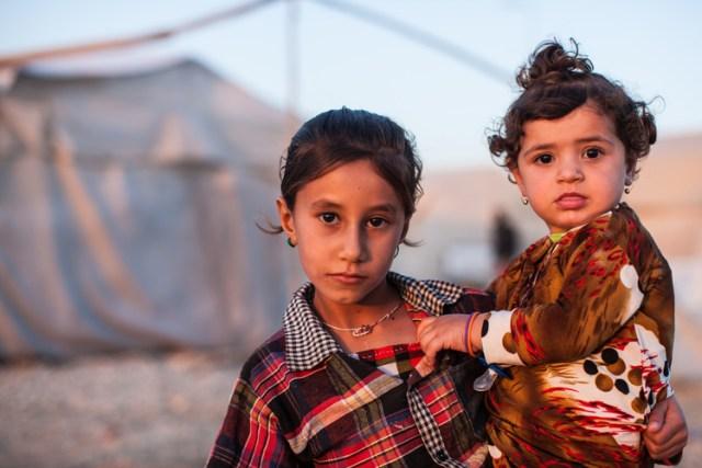 A young Yazidi girl carries her sister in Shariya IDP camp.