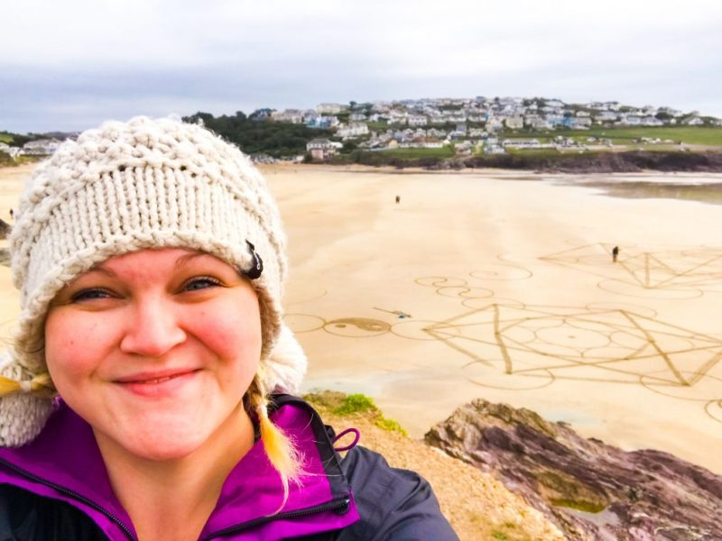 A close up of Bex and in the background is an aerial shot of the beach art.