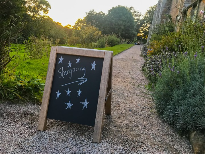 A sign directing people to stargazing at Trerice - it's a black chalkboard with stars drawn in chalk.