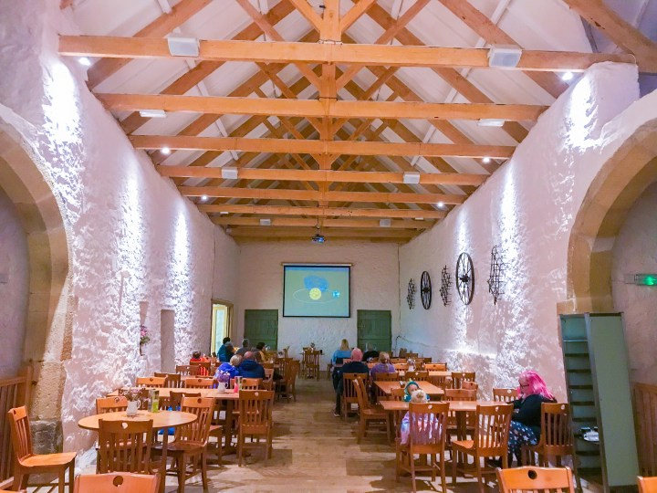 The beautiful white barn with big wooden ceiling beams. There's a projector at the end off the room and big tables either side of a central aisle in the long barn.
