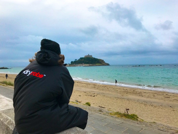 Bex from Bright Lights Big City in her Long Sleeve dryrobe sat on the beach looking out at St Michael's Mount.
