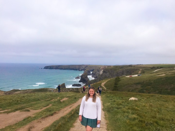 Bex stood on the trail in a relaxed pose with a cheesy grin at Carnewas aka The Bedruthan Steps