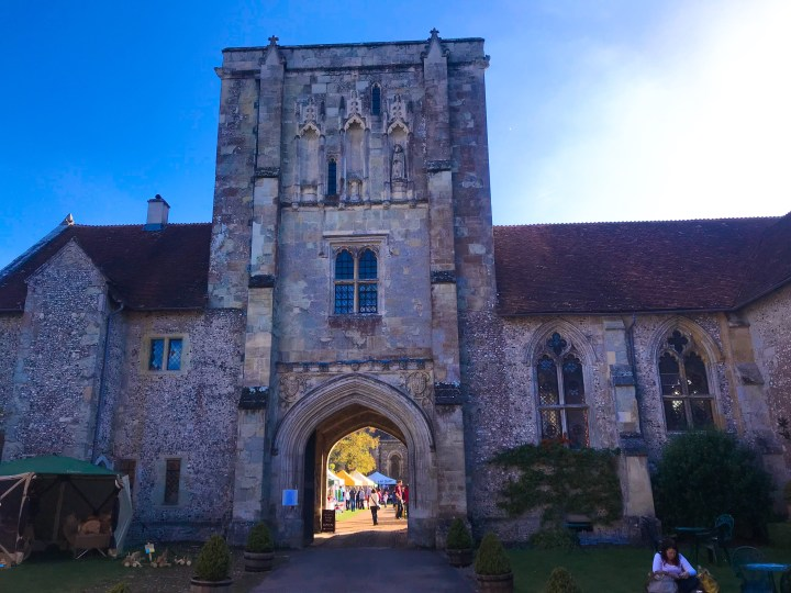 The entrance to The Hospital of St Cross in Winchester, a large stone building with stained glass, arched windows and an archway through to the grounds.