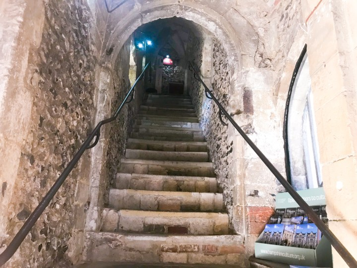 The stone staircase up the Westgate tower into the museum, it's dark and old looking with arch ways and black steel bannisters either side to help climb the uneven steps.