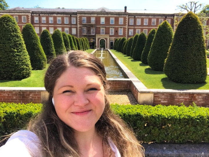 Bex, with her hair down, smiling at the camera, stood in front of an eloquent long water feature with fountains lines with perfectly manicured cone fir trees at the Military Quarter in Winchester
