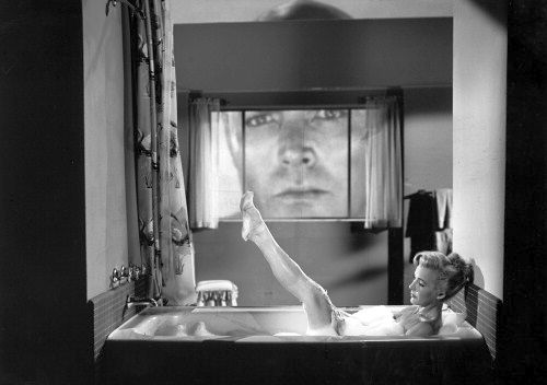 Cathy Downs takes a bath while a rear-projected Glenn Langan watches in The Amazing Colossal Man (1957)