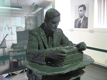 The 1.5 -ton statue of Alan Turing, by Stephen Kettle commissioned by the American billionaire Sidney Frank. This statue at Bletchley Park is made of about half a million pieces of slate quarried in Wales. Photo by Jon Callas, courtesy of Wikimedia Commons