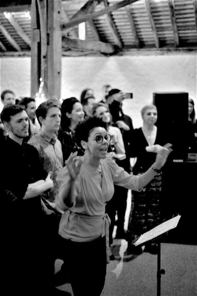 A black and white photo of Amanda Mitchell conducting the Brandwatch choir at their first performance. Behind her are all the party goers who are watching the performance.
