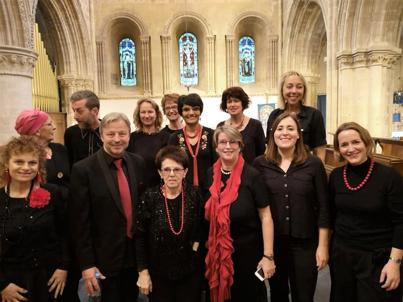 A photo of Bright Soul Choir members dressed in smart black clothes with red accessories. They are standing in a church and getting ready to perform.
