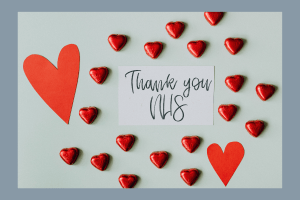 """An image of some grey card with love hearts dotted all over it. In the middle where is some hand writing which say """"Thank yo.u NHS"""""""