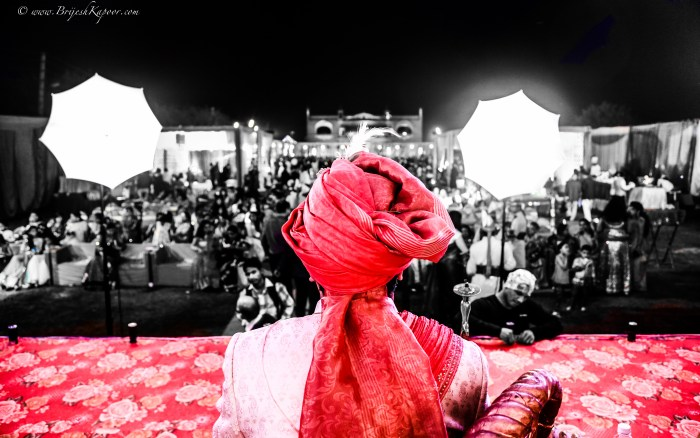 WEDDING PHOTOGRAPHY SHOT BY BRIJESH KAPOOR OF AN INDIAN GROOM WEARING A RED TURBAN SITTING ON A STAGE ON HIS WEDDING DAY WAITING FOR THE BRIDE TO ARRIVE