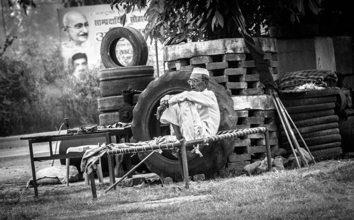 BLACK AND WHITE STREET PORTRAIT OF A VILLAGER SMOKING A CIGARETTE IN RURAL INDIAN WITH MAHATMA GANDHI IN TH BACKGROUND CLICKED BY BRIJESH KAPOOR PHOTOGRAPHY