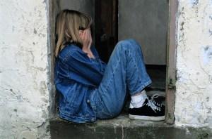 Sad child huddled in doorway