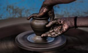 person making pottery on a wheel
