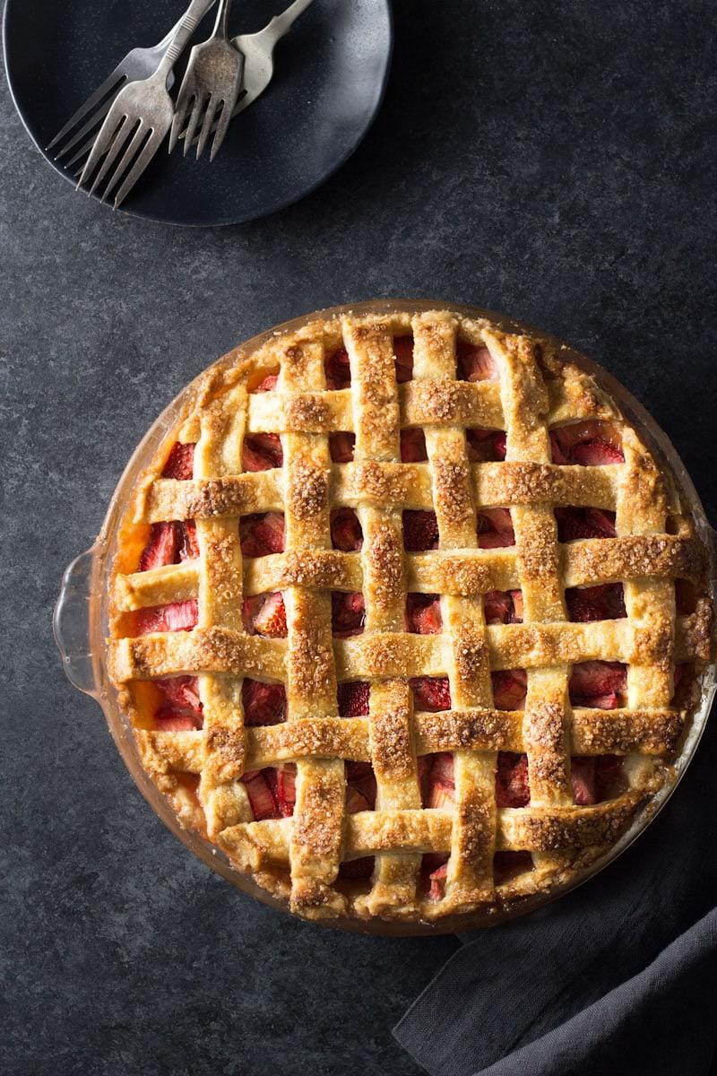 Strawberry Rhubarb Pie overhead with lattice crust on dark grey background