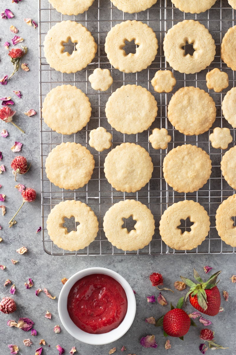 Overhead shot of linzer cookie tops and bottoms on a cooling rack surrounded by a bowl of strawberry rose jam, fresh strawberries and dried flowers and rose petals on a light grey textured surface.