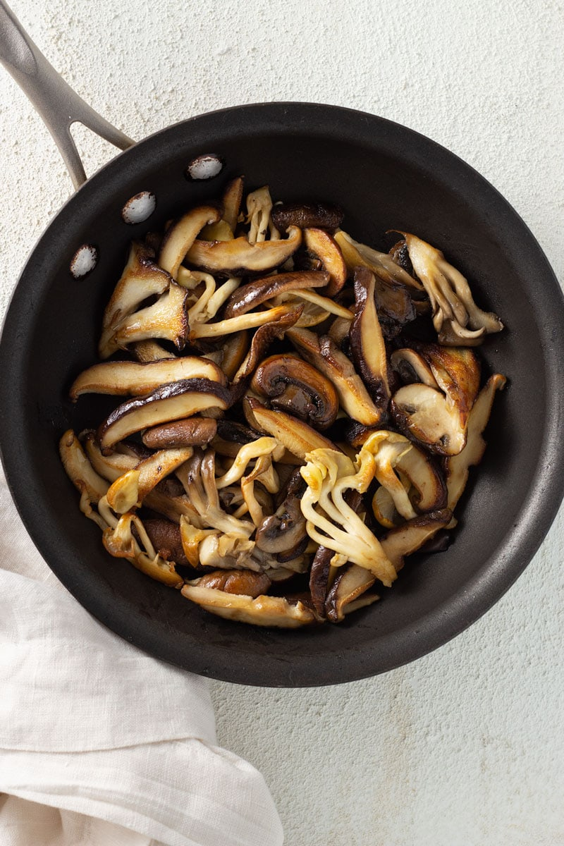 Overhead shot of a mix of mushrooms (maitake, yellow oyster, shiitake and cremini) cooked in a black saute pan on an off white textured surface with an off white napkin.