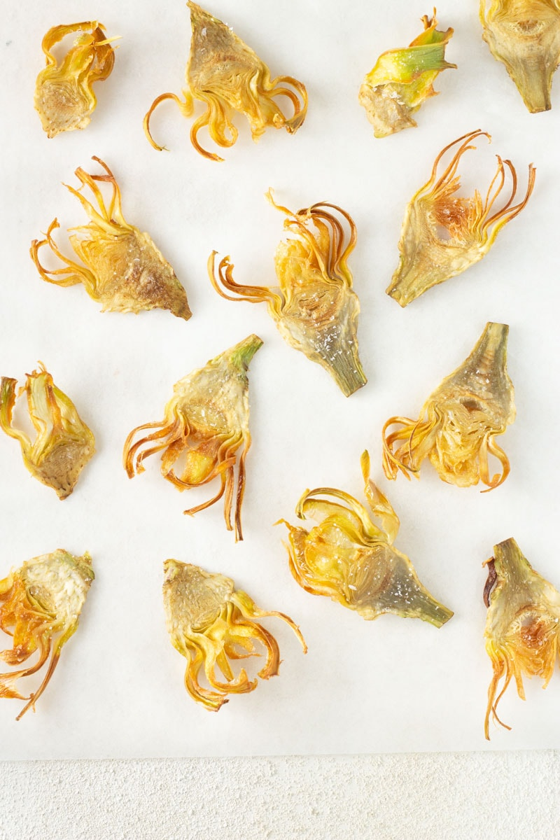 Overhead shot of fried artichoke slices on parchment paper on a white textured surface.