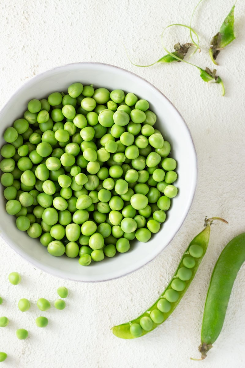 Overhead shot of a white bowl filled with raw peas and surrounded by pea pods and loose peas on a white, textured surface.
