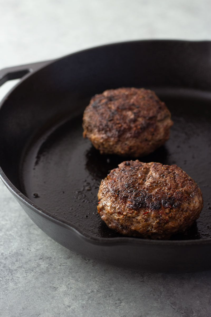 Two harissa lamb burgers in a cast iron pan on a light grey surface.