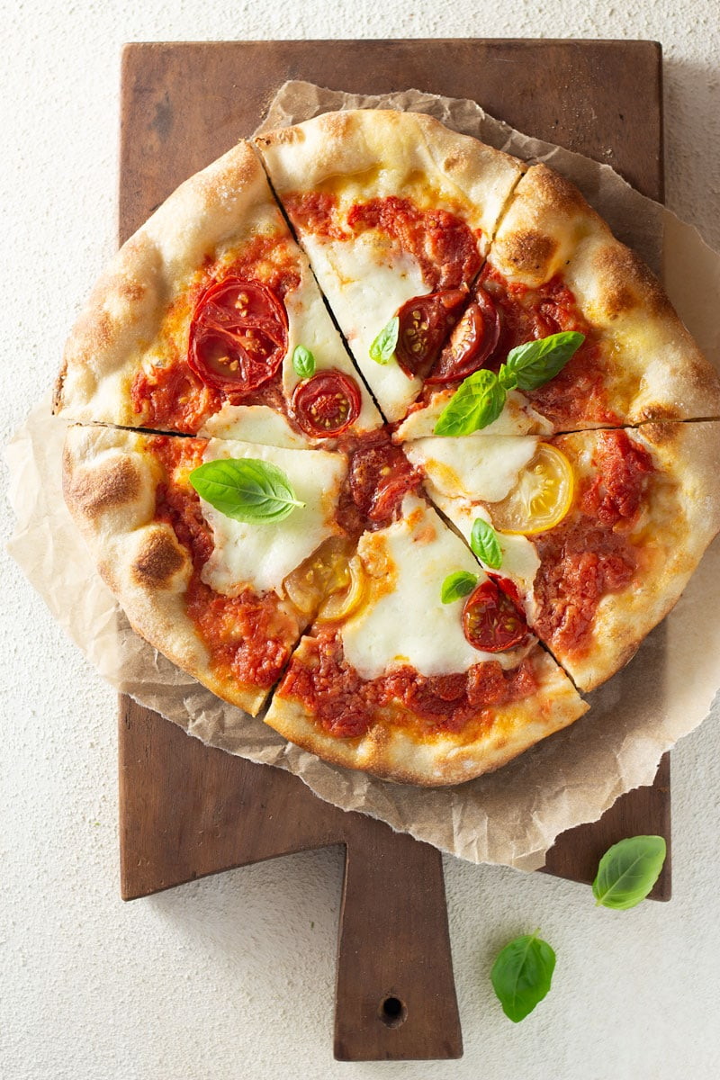 Overhead shot of a margherita pizza topped with colored, heirloom tomatoes, pizza sauce and buffalo mozzarella cheese on parchment on a dark wood French cutting board on an off white, textured surface.