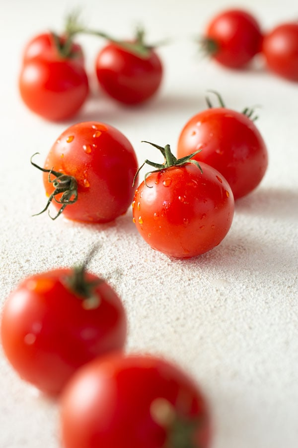 3/4 shot of small fresh tomatoes wet with water droplets on a textured white surface.